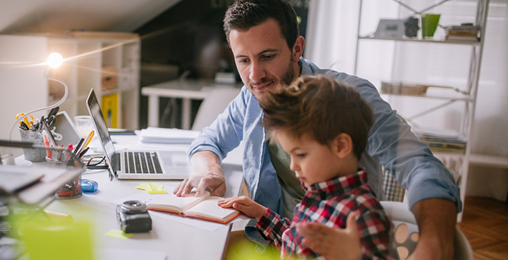 Father helping child with schoolwork while working from home