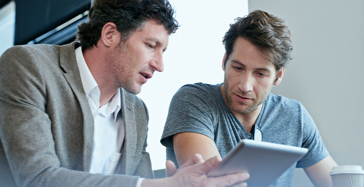 Two IT specialists look at data on a tablet