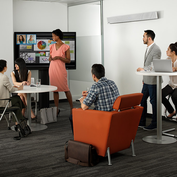 Business professionals using he HDL300 audio conferencing system for a team meeting